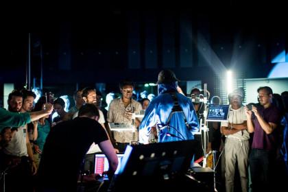 Un concert d'électro en octophonie à la maison de la radio. Le public, enveloppé par une couronne de huit haut-parleurs, est disposé autour des musiciens et des ingénieurs du son. spatialisation NSDOS